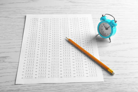 Exam form, pencil and alarm clock on table Stock Photo - 100142673