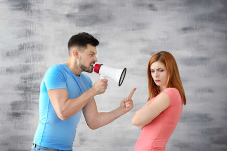 Angry man with megaphone scolding his wife on grey background