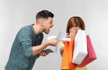 Angry man scolding his wife who has spent a lot of money for shopping, against light background Фото со стока