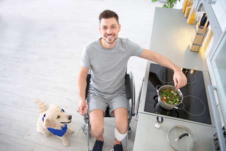 Man in wheelchair cooking with service dog by his side indoors Stock Photo
