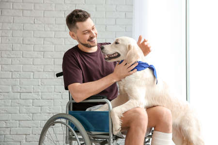 Man in wheelchair with service dog indoors