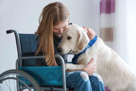 Chica en silla de ruedas con perro de servicio en el interior Foto de archivo