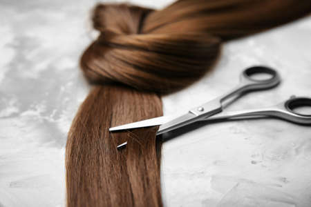 Professional hairdressers scissors and strand of brown hair on grey background