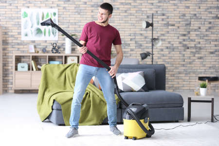 Young man hoovering floor while cleaning flat