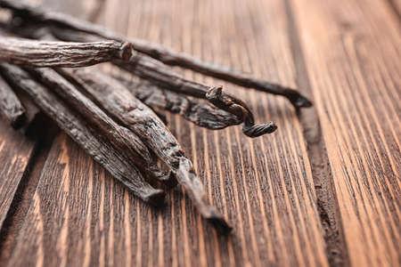 Vanilla sticks on wooden background, closeup
