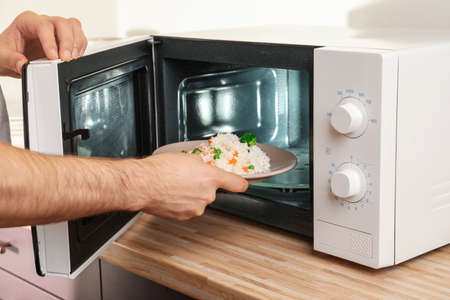 Man putting plate of rice with vegetables in microwave oven, closeup