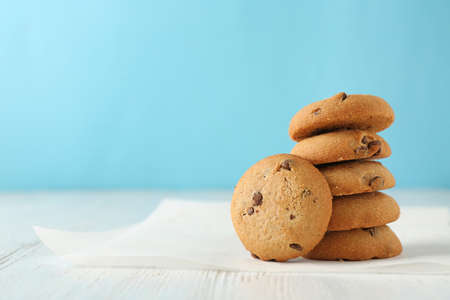 Delicious oatmeal cookies with chocolate chips on wooden table against color background Stockfoto
