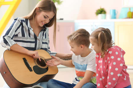 Mother playing guitar for her little children at home