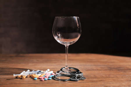 Composition with wineglass, drugs and handcuffs on table. Alcoholism and drug addiction Stock Photo