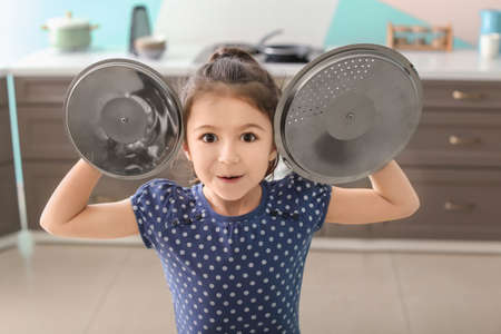 Cute little girl playing with saucepan caps as cymbals in kitchen