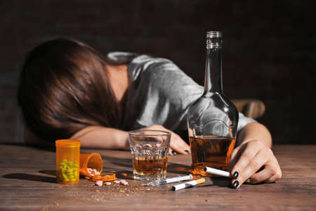 Alcohol, drugs, cigarettes and unconscious woman on background Banque d'images