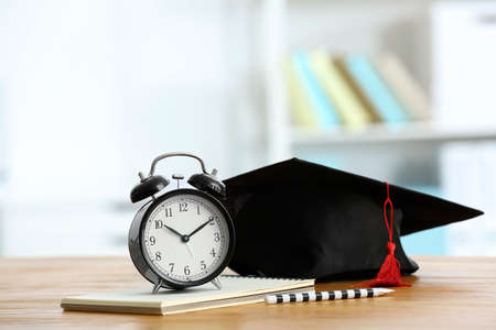Alarm clock and graduation cap on table. Study goals Stock Photo