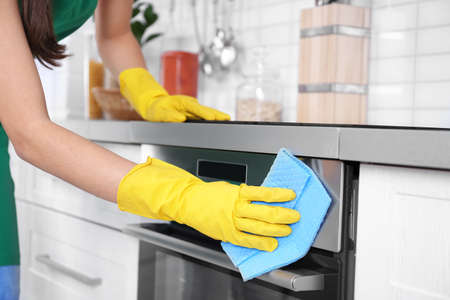 Woman cleaning oven in kitchen, closeup Stock Photo