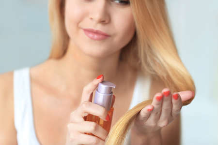 Young woman applying oil onto her hair, indoors Imagens