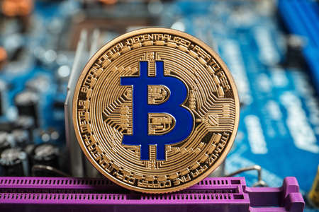 Golden bitcoin on PC motherboard Stock Photo