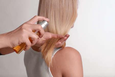 Stylist applying oil onto womans hair on light background