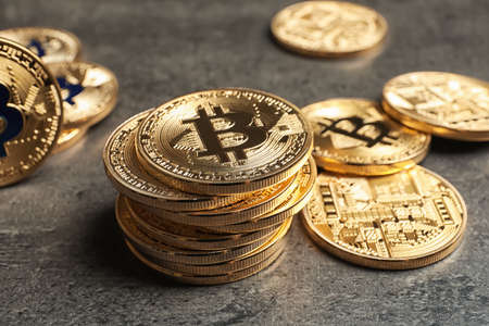 Golden bitcoins on grey background