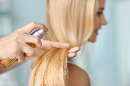 Stylist applying oil onto womans hair, indoors
