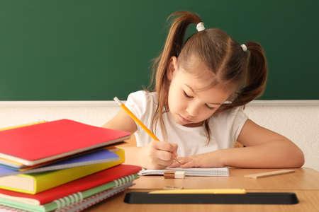 Cute little girl doing homework in classroom Stock Photo