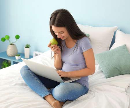 Cute teenager girl using laptop while doing homework in bedroom