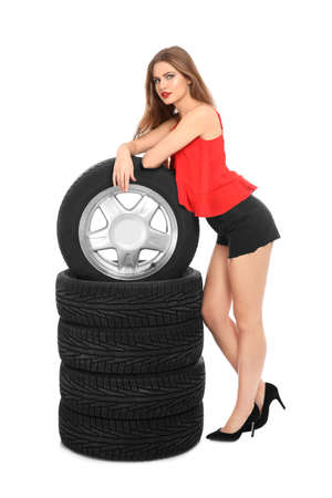 Young woman in seductive outfit with car tires on white background