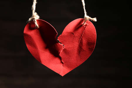 Ripped heart hanging on ropes against dark background. Relationship problems