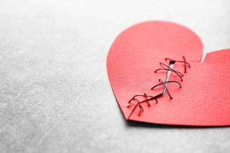 Paper heart cut in half and sewn back together on light background. Relationship problems