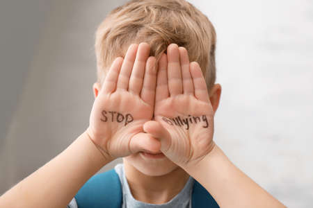 Little boy with words Stop bullying on light background