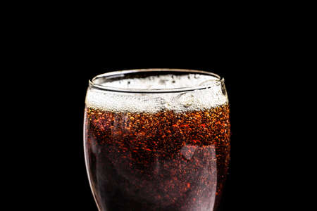 Glass of refreshing cola on black background, closeup