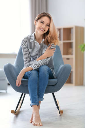 Happy young woman sitting in armchair at home