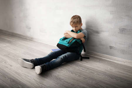 Upset little boy with backpack sitting on floor indoors. Bullying in school