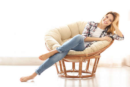 Happy young woman relaxing in armchair at home