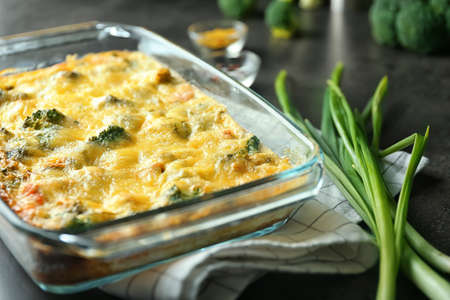 Glass baking dish with tasty broccoli casserole on table. Fresh from oven