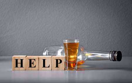 Strong drink and cubes with word HELP on table. Concept of alcoholism