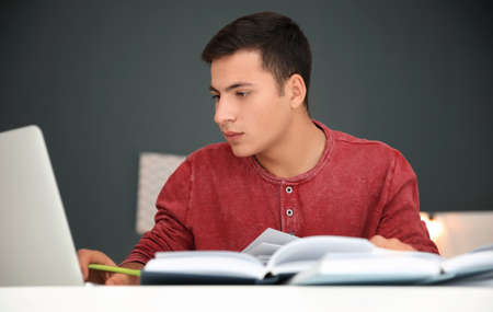 Male student preparing for exam at table indoors