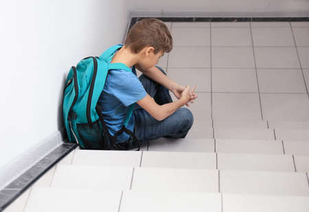 Sad little boy with backpack sitting on stairs. Bullying in school
