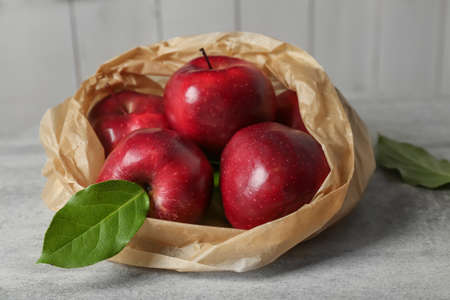 Paper bag with ripe red apples on table