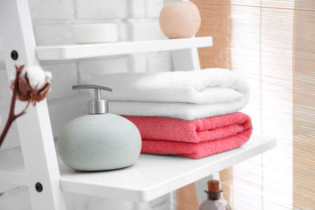 Clean towels with soap dispenser on shelf in bathroom Stock Photo
