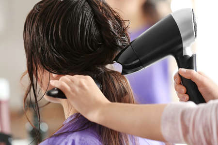 Professional hairdresser working with client in salon Stock Photo