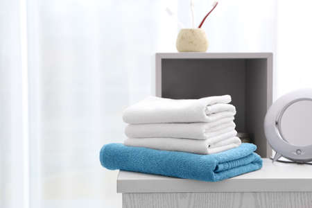 Stack of clean towels on table in bathroom Stock Photo