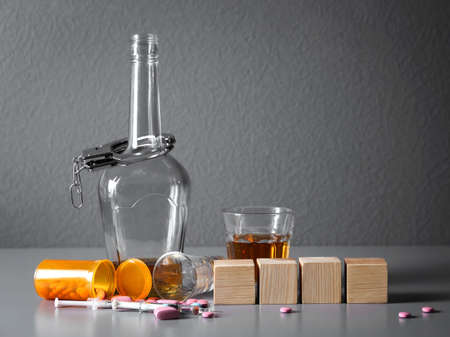 Strong drink, drugs, handcuffs and cubes with space for text on table. Concept of alcoholism