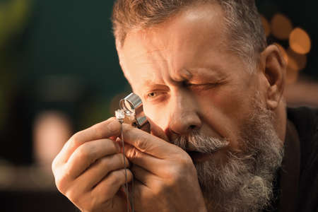 Jeweler evaluating gem with magnifier at workshop Stock Photo
