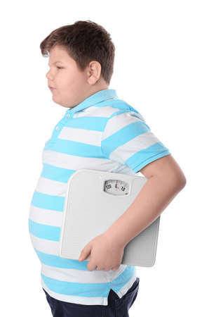 Overweight boy with floor scales on white background