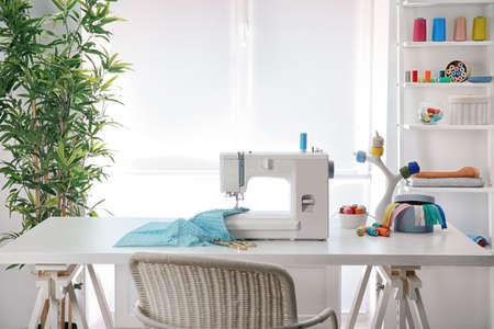 Maszyna do szycia z tkaniną na stole w pracowni krawieckiej