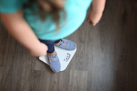 Overweight girl standing on floor scales indoors Stock Photo