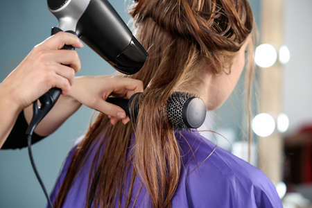 Professional hairdresser working with client in salon, closeup