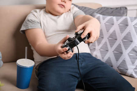 Overweight boy playing videogame indoors