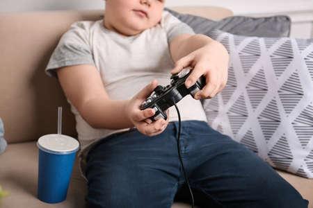 Ragazzo in sovrappeso che gioca videogioco al chiuso