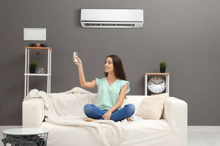 Young woman switching on air conditioner while sitting on sofa at home Stock Photo - 101022639