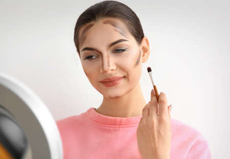 Young woman applying contouring lines on her face against light background. Professional makeup products